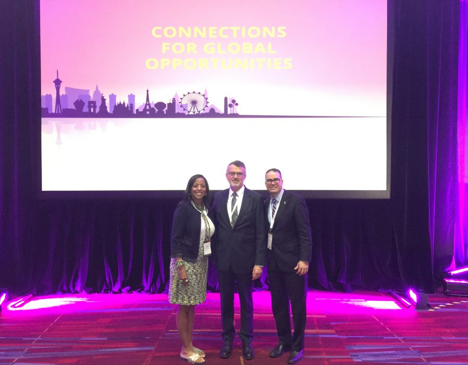 Denise Thomas (left), director of Africa and Middle East Trade and Melvin Torres (right), director of Latin America Trade stand with Scott Ferguson, president of the World Trade Centers Association at the General Assembly.