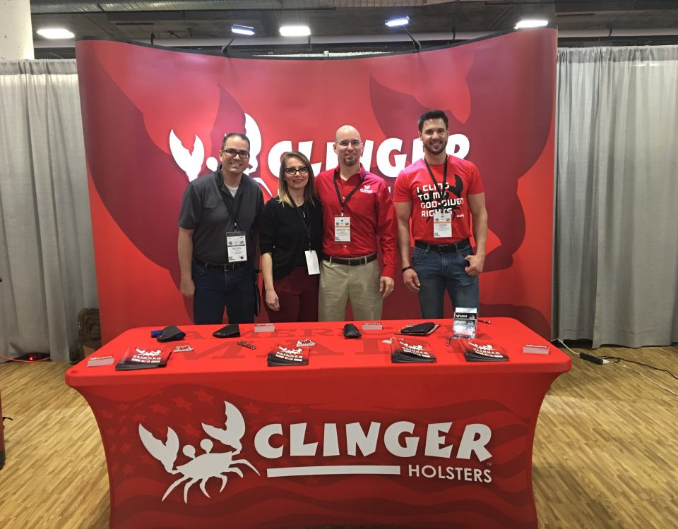 Melvin Torres (left) stands with the Clinger Holsters team at SHOT Show. Chris (middle right) and Sherry (middle left) Tedder operate their business out of Van Buren, Arkansas.